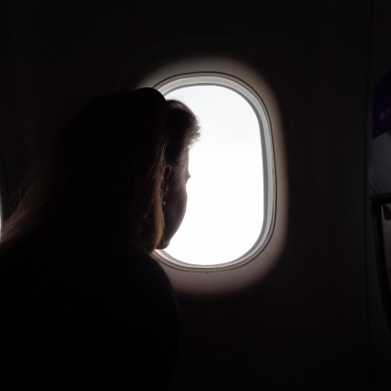 Woman. Seated on Aeroplane. Pensive.   (c) Holly Maxwell Boydell   www.TheHollyTreeTales.com